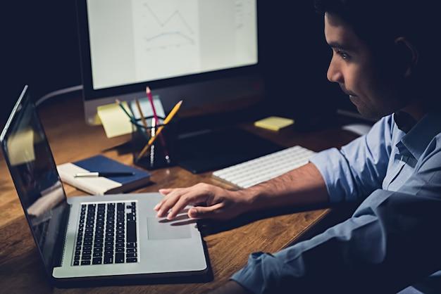 Zakenman die overuren laat in de nacht in het kantoor blijven die zich bij het werken met notitieboekjecomputer concentreren