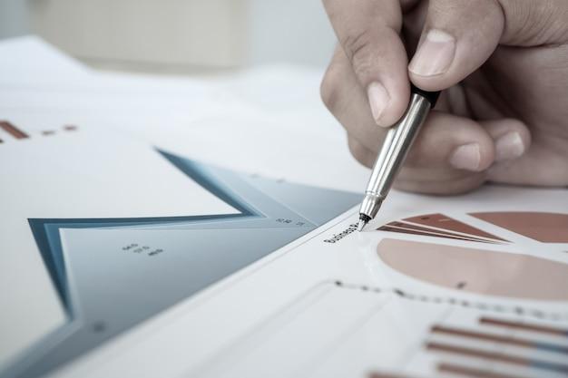 Zakenman die pen vasthoudt voor het lezen van ondertekeningsdocumenten met rapportgrafiekmarketing of zakelijke rapporten op kantoor.