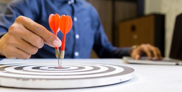 Zakenman die pijltjes houden die naar het doelcentrum streven, het concept van het bedrijfs de groeisucces.