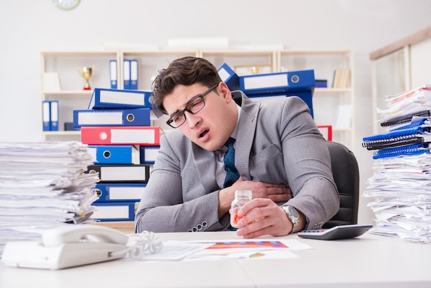 Zakenman die pillen neemt om aan spanning het hoofd te bieden