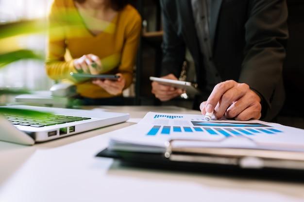 Zakenman die presentatie maakt met zijn collega's en zakelijke tablet digitale computer op kantoor als concept in ochtendlicht