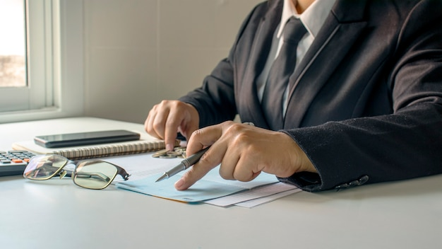 Zakenman die rekeningen en bedrijfsinkomsten, het concept van financieel beheer en financiering controleert.