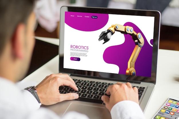 Zakenman die robotica-website met laptop doorbladert