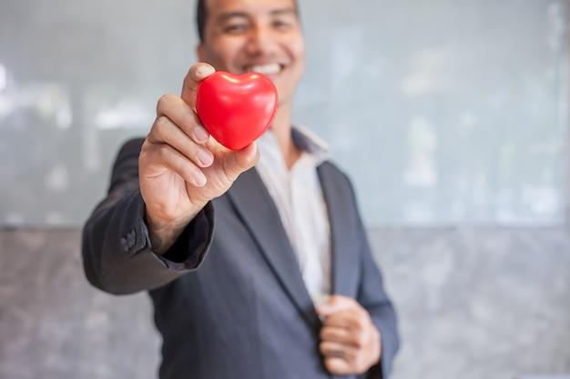 Zakenman die rood hart houdt. het concept van het werk uit het hoofd.