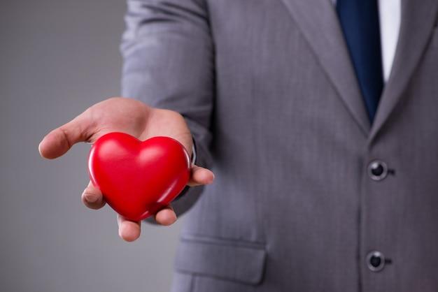 Zakenman die rood hart in liefdeconcept houdt