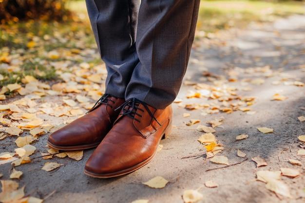Zakenman die schoenen in de herfstpark draagt. bruin lederen klassieke schoenen. close up van benen