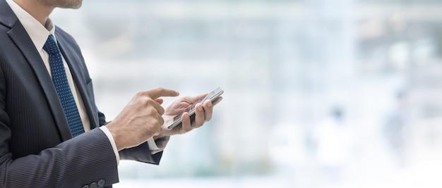 Zakenman die slimme telefoon op binnenlandse de bannerachtergrond van het onduidelijk beeldwinkelcomplex gebruiken