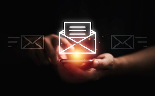 Zakenman die smartphone gebruikt om e-mail te openen voor zakelijk contact en communicatieconcept.
