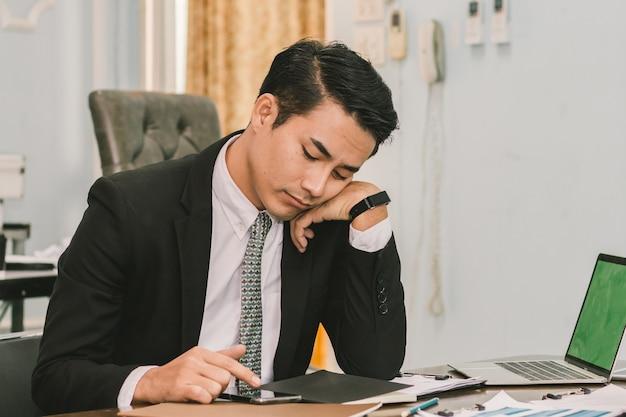 Zakenman die smartphone in het bureau gebruikt