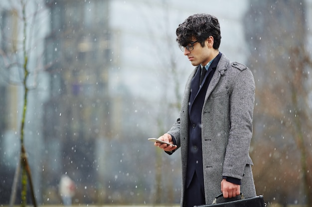 Zakenman die smartphone in sneeuwstraat gebruikt