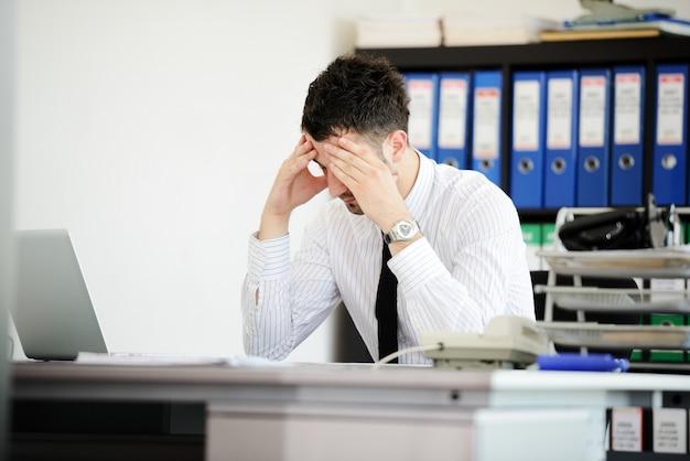 Zakenman die spanning in het bureau hebben