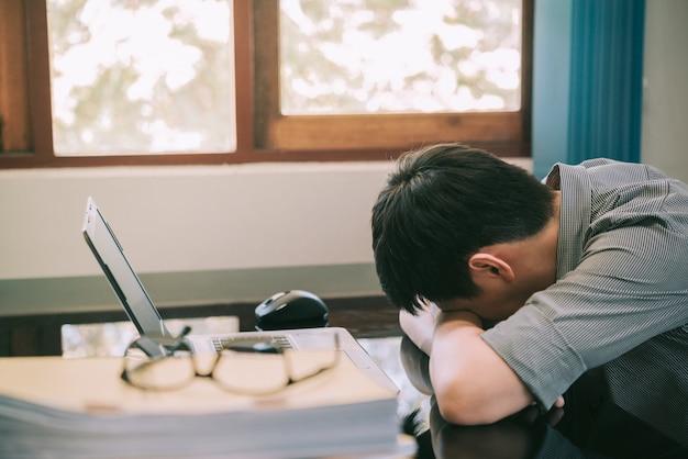 Zakenman die spanning met laptop computer hebben die in het bureau, spanning en overwerken werken