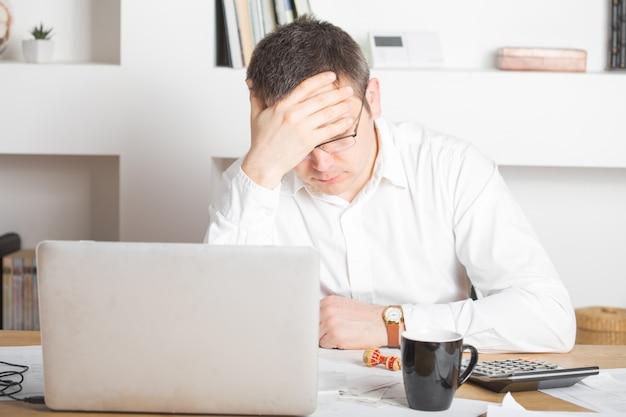 Zakenman die spanning met laptop computer hebben die in het bureau werken, de kaukasische mens wat betreft zijn hoofd, heeft hij een slechte hoofdpijn, een spanning en een overwerkconcept.