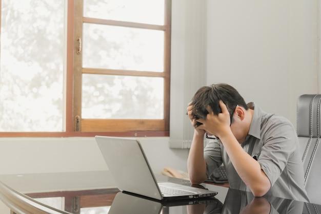 Zakenman die spanning met laptop computer heeft die in het bureau werkt