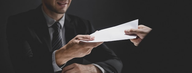 Zakenman die steekpenningsgeld in de envelop geven om samen te brengen