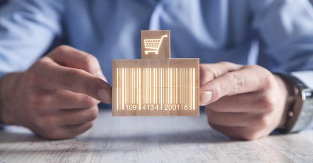 Zakenman die streepjescode met boodschappenwagentje toont