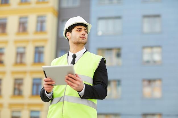 Zakenman die tablet gebruikt bij bouwwerf