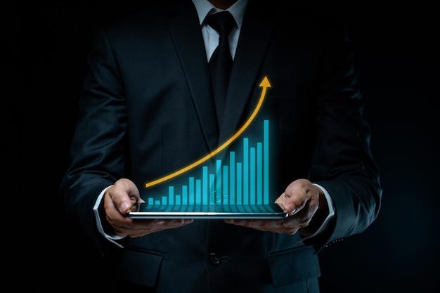 Zakenman die tablet gebruikt die digitale marketing met grafiekhologrameffect plant