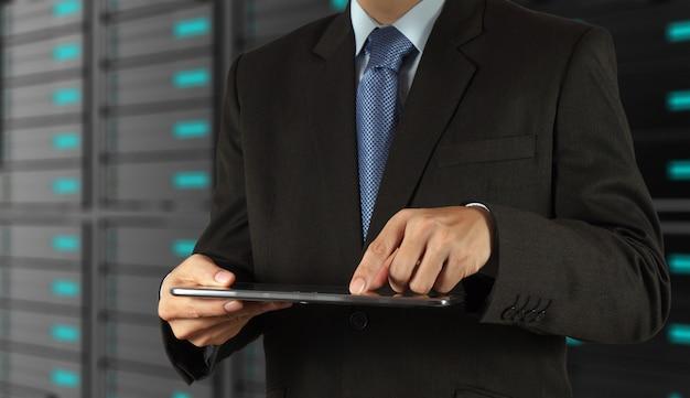 Zakenman die tabletcomputer en serverruimteachtergrond met behulp van