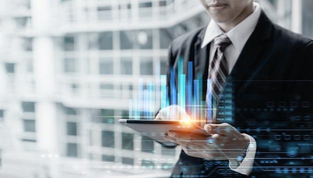 Zakenman die tabletcomputer gebruikt voor analysegrafiekgegevens van beurs, zaken en financiënconcept.