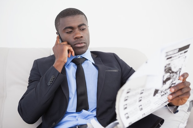 Zakenman die telefoneert terwijl het lezen van het document op bank