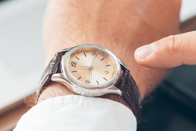 Zakenman die tijd dicht op zijn horloge controleren