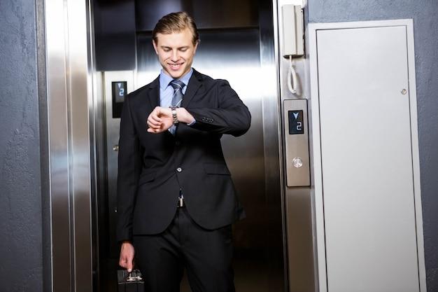 Zakenman die tijd in lift in bureau controleert
