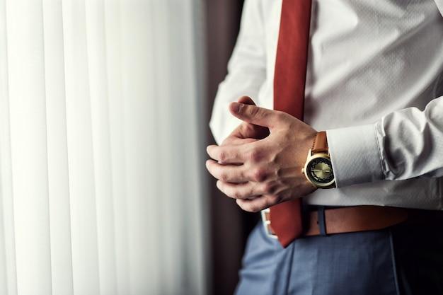Zakenman die tijd op zijn polshorloge controleert, mens die klok bij de hand zet, bruidegom die klaar in de ochtend vóór huwelijksceremonie wordt
