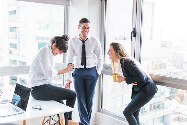 Zakenman die twee onderneemster bekijkt die in het bureau lacht