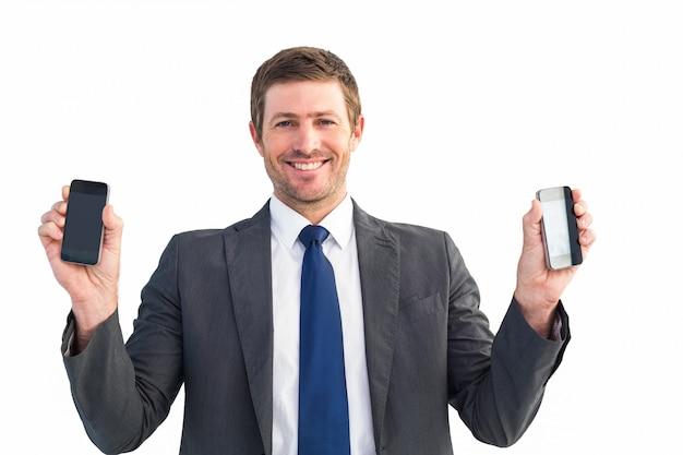 Zakenman die twee slimme telefoons houdt