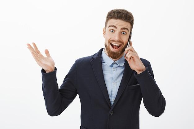 Zakenman die uitstekend nieuws ontvangt. blij en opgewonden opgetogen goed uitziende mannelijke ondernemer in elegant pak met smartphone in de buurt van oor praten, opgewekt hand opsteken en glimlachen van vreugde