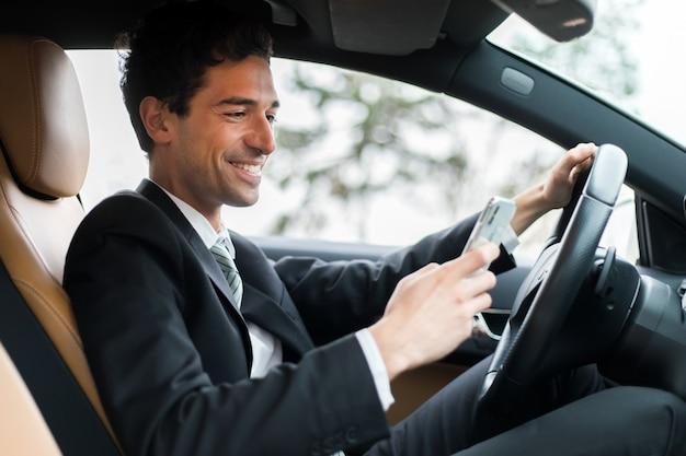 Zakenman die veiligheid negeert en op mobiele telefoon texting terwijl het drijven