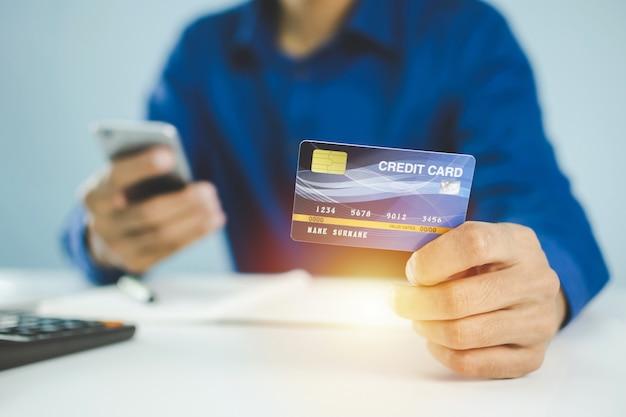 Zakenman die veiligheidscode met mobiele telefoon ingaat en met creditcard betaalt