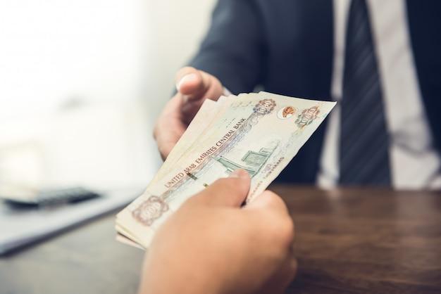Zakenman die verenigde arabische emiraten dirham geldbankbiljetten geven aan zijn partner
