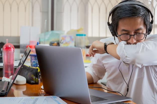 Zakenman die videoconferentie maakt en niest in elleboog. concept stopt met het verspreiden van coronavirus.
