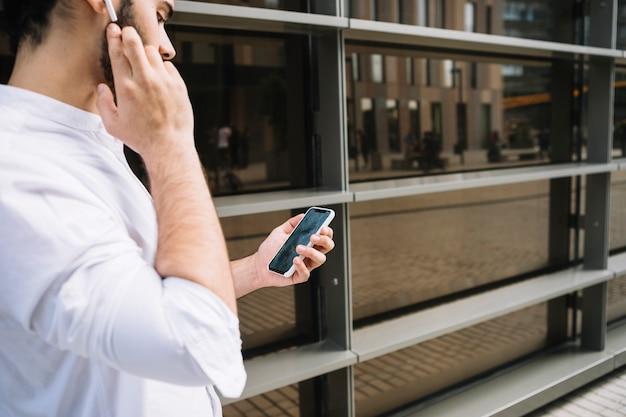 Zakenman die videoconferentie op smartphone doen en met bluetooth handsfree apparaat spreken
