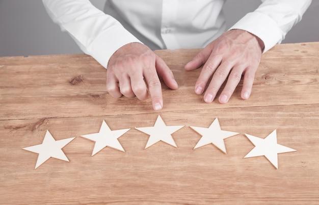 Zakenman die vijfsterrenclassificatie toont. klantenservice ervaring en tevredenheid