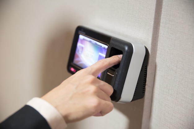 Zakenman die vingerafdruk gebruiken om deur te openen.