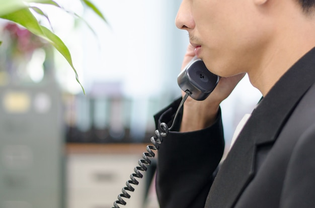 Zakenman die voip telefoon in het bureau draait