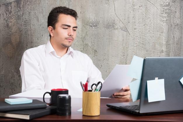 Zakenman die werkdocumenten bij het bureau kijkt.