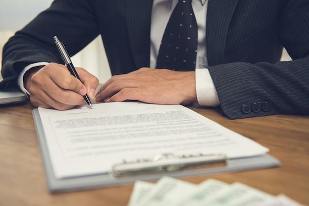 Zakenman die wettelijke bedrijfscontractovereenkomst ondertekent