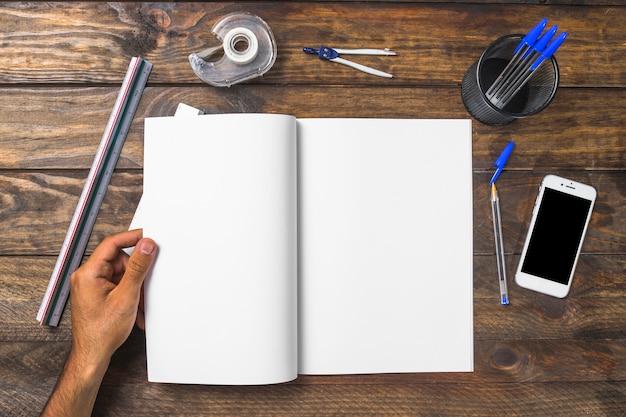Zakenman die witboek houdt dat met stationeries en cellphone wordt omringd