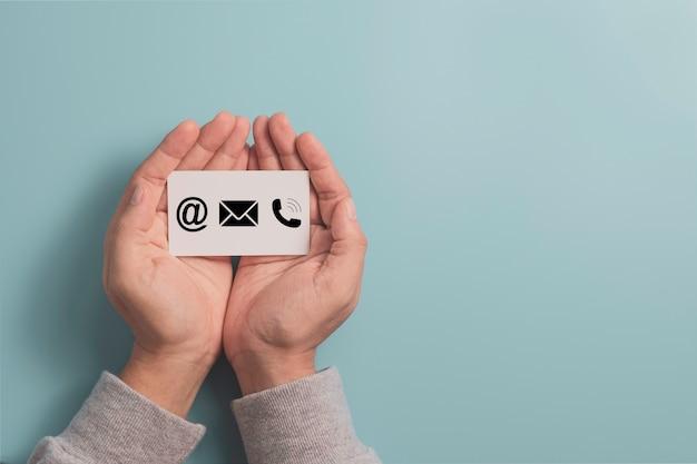 Zakenman die zakelijk contact houdt dat wit papier op het scherm afdrukt, inclusief e-mailadres en telefoonnummer.