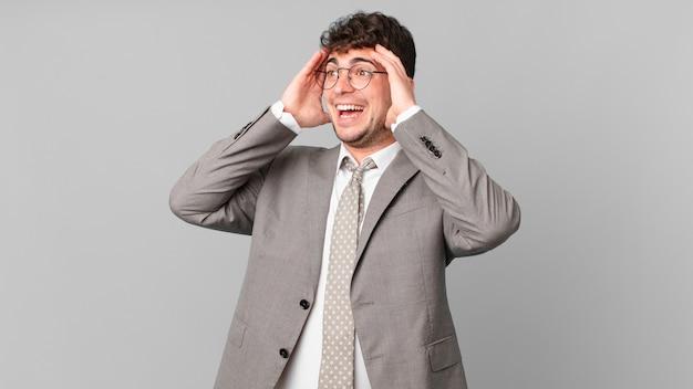 Zakenman die zich gelukkig, opgewonden en verrast voelt, opzij kijkend met beide handen op het gezicht