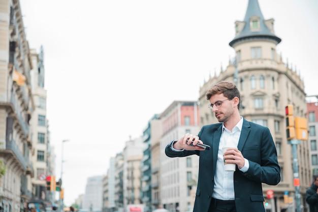 Zakenman die zich op stadsstraat het letten op tijd op zijn polshorloge bevindt