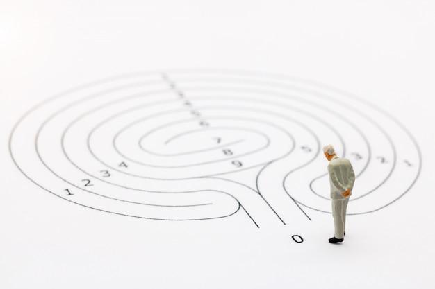 Zakenman die zich op startpunt van labyrint bevinden en denken hoe te om dit probleem op te lossen.