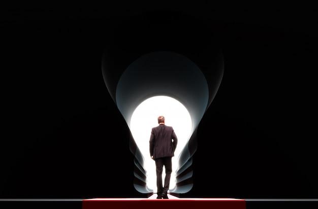 Zakenman die zich voor de grote deur van de idee gloeilamp bevinden. concept zakelijk succes.