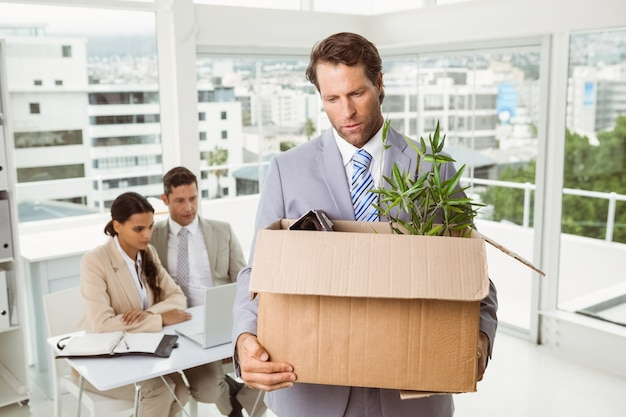 Zakenman die zijn bezittingen in doos draagt