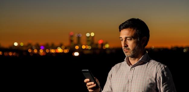 Zakenman die zijn celtelefoon bekijkt aangezien de zon op de horizon in de muur ondergaat