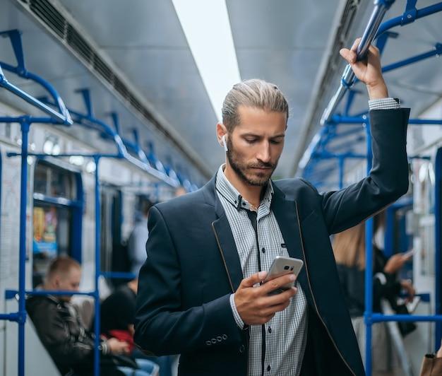 Zakenman die zijn e-mailcorrespondentie in de metro leest